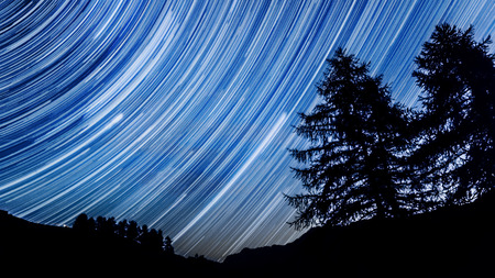 nebulous: Star trail effect over mountain and trees in night sky