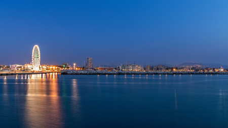 Rimini waterfront cityscape at evening. Urban night lights