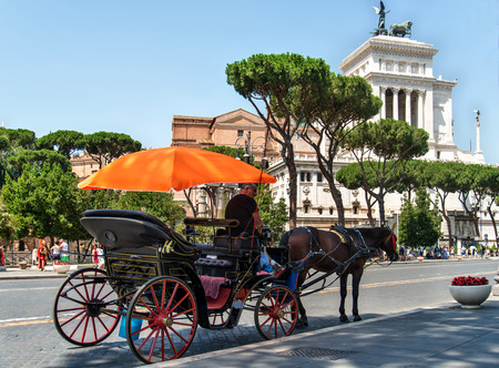 coachman: ROMA, ITALY, JULY 3, 2016 : Coachman sits on a carriage, pulled by a horse, waiting for tourists. Imperial fora street Editorial