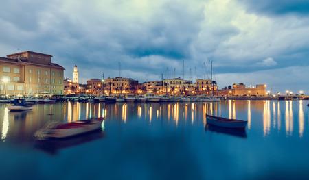 バーリ海辺のマリーナからのシティビュー。青い海と曇り空。長時間露光フィルター画像 写真素材