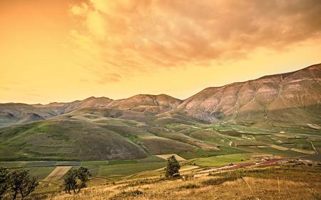 Warme zonsondergang landschap. Bergen en velden achtergrond. Italië