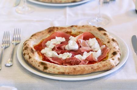 Italian Pizza with ham and mozzarella cheese. Close up table set interior restaurant