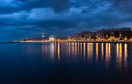 Bari Italië nacht cityscape kustlijn van zee. Citylights aan de kust bij zonsondergang