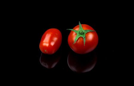 cherry and datterino tomato on black background. fresh biological food Stockfoto