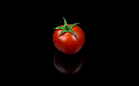 Fresh cherry tomato single on black background