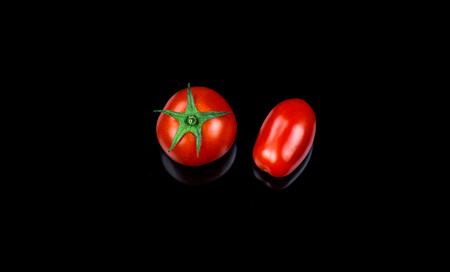 kers en datterino tomaat op zwarte achtergrond. vers biologisch voedsel Stockfoto