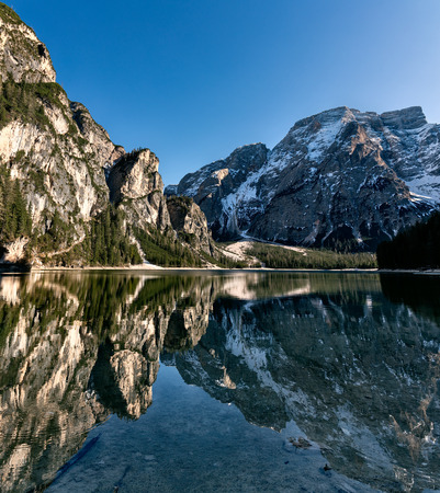 Water reflection mountain lake. Braies Lake Italy at sunset Imagens