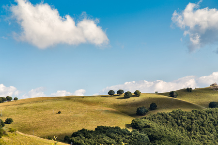 landscape panorama. Hills, grass and clouds over blue sky. Italy mountains