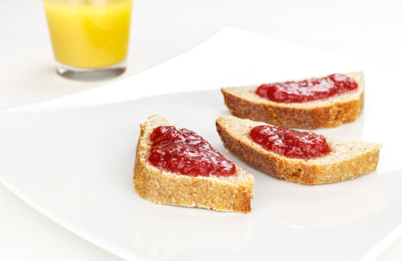 red fruit marmalade on sliced bread on white serving plate and orange juice glass