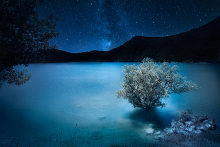 night deep dark blue. Milky way stars over mountain lake. Magic scenic landscape Imagens