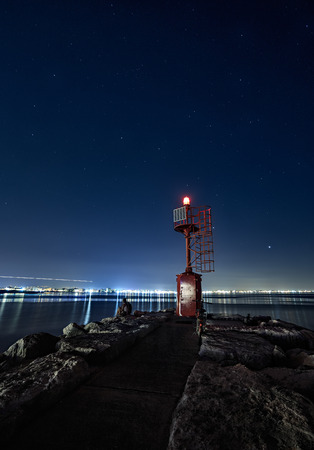 lighthouse and rocks night seascape. City lights after sunset. Rimini Italy. Long exposure Imagens