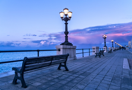 Bari seafront at sunset Purple and blue sky landscape panorama. Bench and street lamp near the sea Stockfoto
