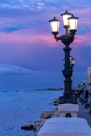 Ancient street lamp on seafront at sunset. Bari, Italy coastline