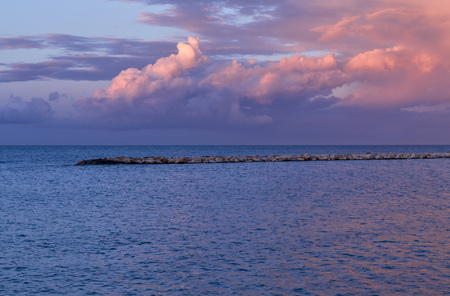 stunning sunset over sea and rocks. Bari seafront coastline. Blue and purple sky and clouds