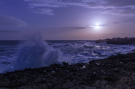 dark blue sunset. Coastline during rough sea. water splash. Stockfoto
