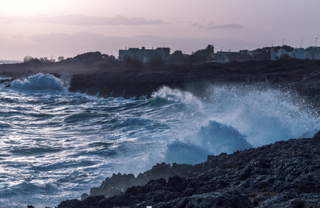 storm seascape at dusk. sunset sea over cliff and rocks. Taranto coastline