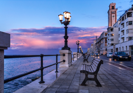 Bari seafront. Colorful amazing sunset. Coastline and city view. Twilight purple and blue sky.
