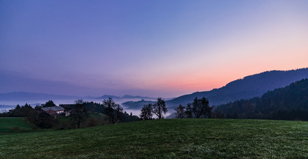 foggy dawn on mountain and valley in Slovenija. Purple sky. Sveti Tomaz church