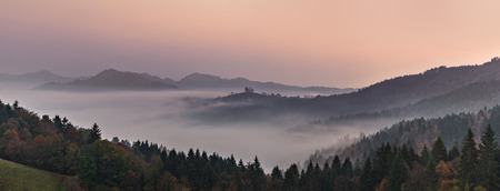 panoramic foggy landscape at dawn over mountain and valley. Slovenia