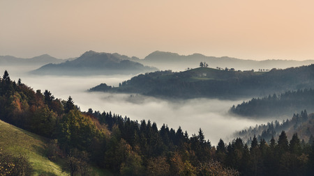 Foggy mountain landscape at dawn. Autumn scenery. Slovenia Sveti Tomaž from hill. sunrise Stockfoto
