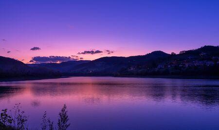 purple sky at sunset over mountain and lake landscape Zdjęcie Seryjne