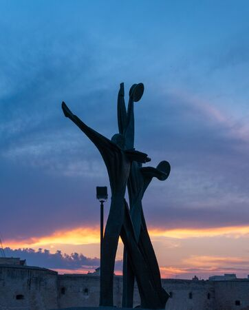 Taranto, Puglia, Italy - 10 august 2018: Silhouette Monument to the Sailor made in bronze in 1974 by the sculptor Vittorio Di Cobertaldo at sunset