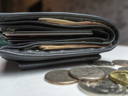Black purse with paper and iron money on white backgraund