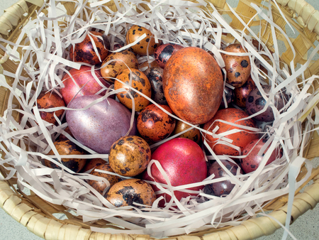 Painted chicken and quail eggs in a basket