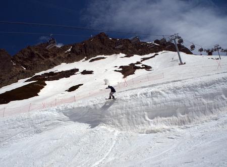 Guy snowboarder jumps on a springboard the ski resort Gorky-gorod. Russia Sochi 05.11.2019