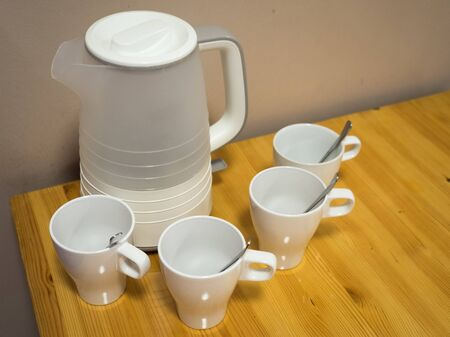 White electric kettle and four white ceramic mugs with teaspoons on wooden table