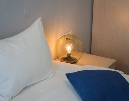 A beautiful round lamp shines near the bedside table