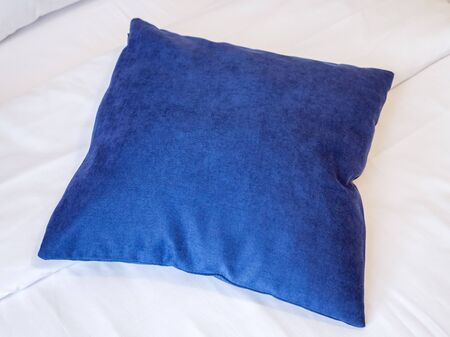 Blue pillow on a white bed sheet in a room