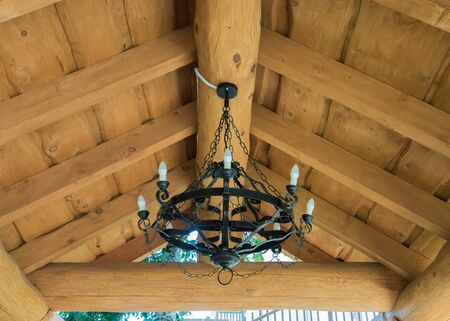 Round black wrought iron chandelier with bulbs weighs in the summer house