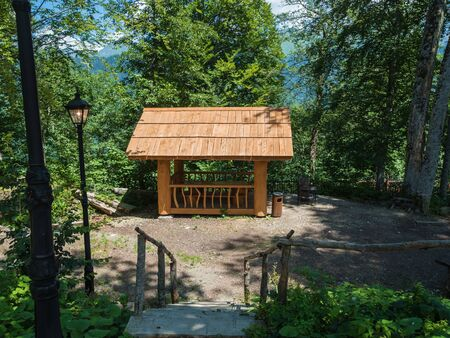 Beautiful summer housefrom a log of a large tree with barbecue for barbecue in the forest Stock fotó