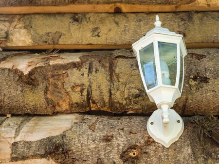 White classic sconce lamp on a round wood wall on the street