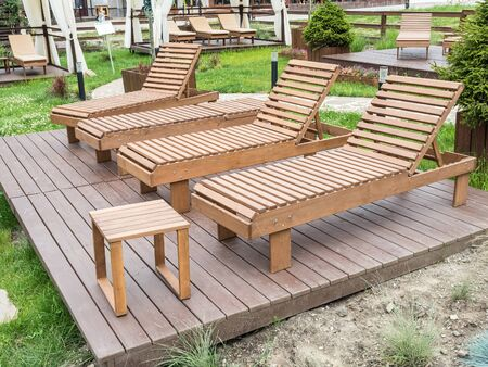 Wooden sunbeds for relaxing in park at Rosa Khutor