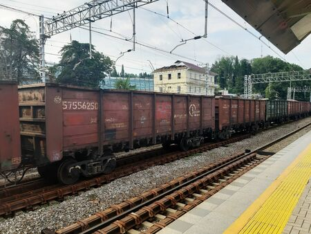 A long train of brown wagons stand on the railway of Sochi station, Russia 07.26.2019 版權商用圖片