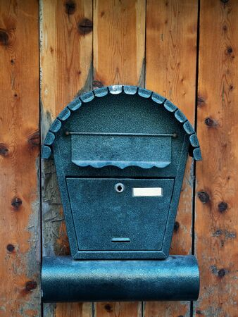 Mailbox for newspapers and letters on wooden door