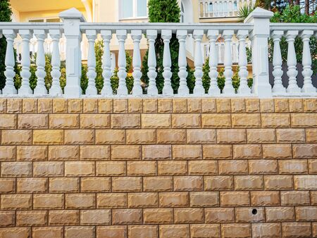 Fence with decorative stone and white balusters