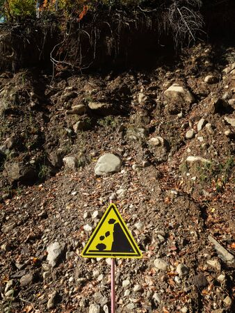 Yellow triangular warning sign stands on hillside background Stock Photo