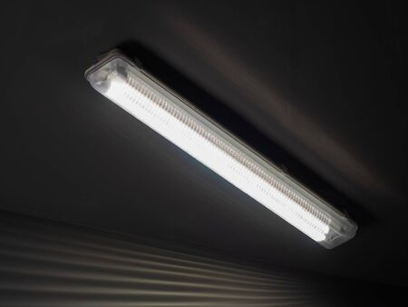 Close-up photo of a long luminous lamp hanging on a dark ceiling