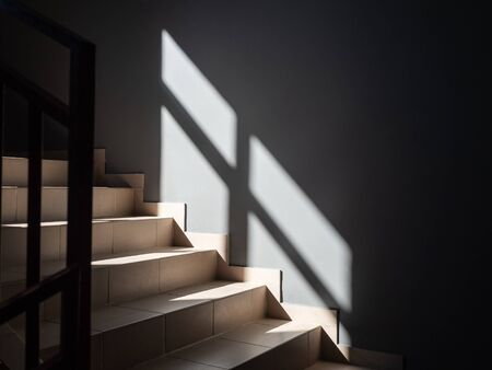 Photos of light steps and gray wall partially illuminated by the sun from the window and with the falling shadow