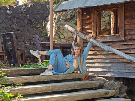 Sochi, Russia - 13 October 2019. A girl in a blue denim suit sits on a wooden staircase holding on to the railing near the wooden hut 新聞圖片