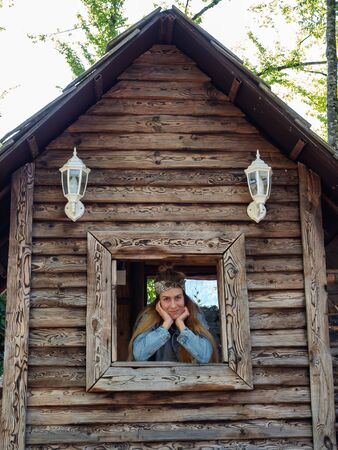 Sochi, Russia - 13 October 2019. The girl looks out of the window of a wooden hut, propping her head with her palms 新聞圖片
