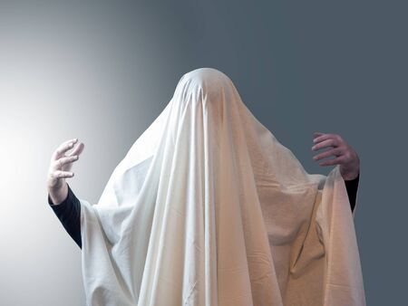 The man, covered in white drapery like a ghost, pulled his hands out from under it against a gray background with light on the left