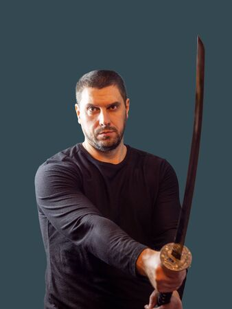 A stern man in dark clothes holds a sword in front of him on a gray-blue background Stock Photo