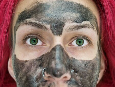 Close-up photo of a fragment of the face of a girl with bright green eyes, red hair and a black peel off mask on her face Foto de archivo