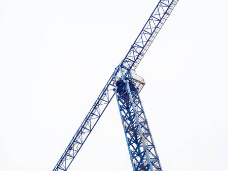 Tall blue tower crane for building houses on a cloudy sky background