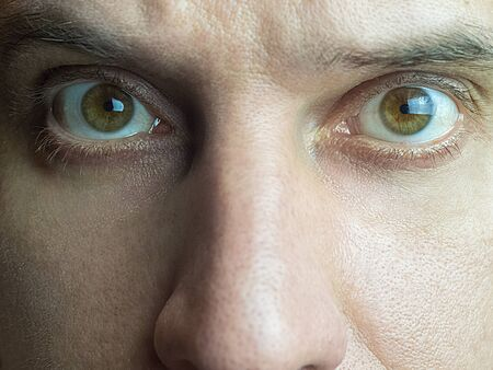 Close-up photo of a fragment of a male face with focus on brown eyes