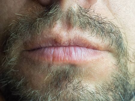 Close-up photo of lower part of the male face lips and beard